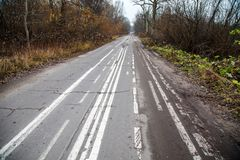 Old abandoned asphalt road with spoiled road markings Stock Photography