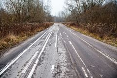 Old abandoned asphalt road with spoiled road markings Stock Photos