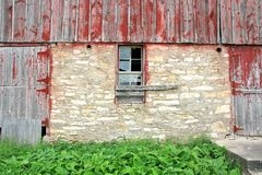 Old Abandoned Barn with Broken Window and Two Wood Doors Royalty Free Stock Images