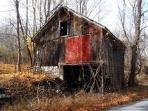 Old Abandoned Barn. Decrepit barn on abandoned farm now gone back to forest  near a rural road Royalty Free Stock Photography