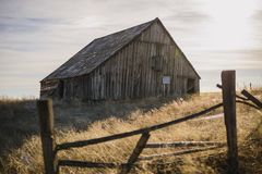 Abandoned barn. An old abandoned barn standing in the glow of a late afternoon behind a rickety fence royalty free stock image