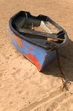 Old abandoned boat. Old boat with peeling paint abandoned on the sand Stock Images