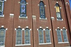 Old abandoned brick  church  with stained glass windows. Old abandoned brick church  with stained glass windows and a damaged windows Royalty Free Stock Images