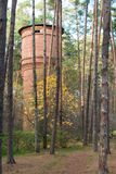 Old abandoned brick water tower in the autumn forest Stock Photo