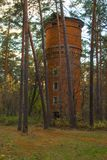 Old abandoned brick water tower in the autumn forest Stock Image