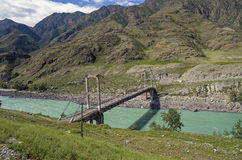 Old abandoned bridge over the river Katun, Altai, Russia. Royalty Free Stock Photo