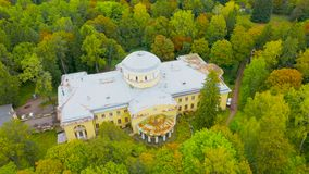 Old abandoned building in the autumn park among bright colored trees, aerial view.  stock video footage