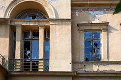 An old abandoned building with a faded facade and broken window Royalty Free Stock Photo