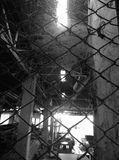 The old abandoned building through the mesh fence . Royalty Free Stock Photos