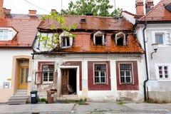 Old abandoned building rainy weather, Maribor street, Slovenia. Squalid abandoned old building exterior wet house, rainy weather, Maribor town city street Royalty Free Stock Photos