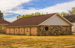 Old Abandoned Building With River Rock Siding. Abandoned Building With River Rock Siding & Six Double Doors Stock Image
