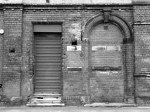 Old abandoned building with shutter and bricked up door Royalty Free Stock Photos