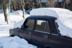 Old abandoned car covered with several layers of snow Royalty Free Stock Images