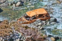Old and abandoned car in the river Stock Photos