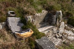 An old abandoned car seat left in the middle of a hillside surrounded by shrubs and weeds, likely used as a hangout for kids. Nobody in the image royalty free stock photography