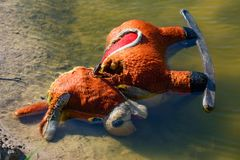 Old abandoned children`s toy donkey in water close stock photo