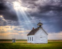 Old Abandoned Church at Sunset. A beam of light shines down on an old abandoned church in a field stock photography