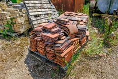 Old abandoned clay roof tiles lying on a pallet in an old yard. Stack of bricks in the background Stock Photos