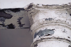 Old abandoned cracked column capital with peel of the paint. Fragment Stock Photos