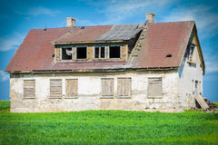 Old abandoned damaged house on grass field Royalty Free Stock Image