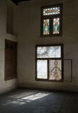 Old abandoned dark damaged dirty room with two wooden broken ornate windows. Covered by interleaved wooden grid mashrabiya Royalty Free Stock Image