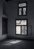 Old abandoned dark damaged dirty room with two wooden broken ornate windows. Covered by interleaved wooden grid mashrabiya. Black and white shot Stock Images