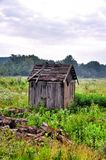 Old abandoned destroyed a barn in a green field Royalty Free Stock Images