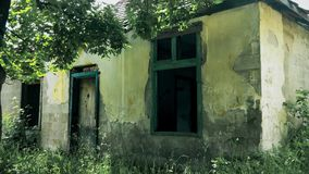 Old abandoned and destroyed house in a mountain among trees. This is footage of Old abandoned and destroyed house in a mountain among trees stock footage