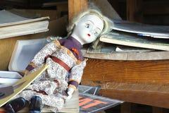 Old abandoned doll on shelf Stock Photo