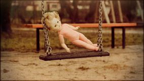 Old abandoned doll on a swing at outdoors in retro style stock video