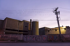 Old abandoned factory at dusk Stock Images