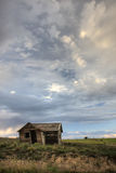Old abandoned farm house on Colorado prairie. With green harvested alfalfa fields in background and stormy sky royalty free stock photos