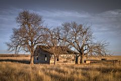 Old abandoned farmhouse on the prairie of Colorado at sunset. The house looks very old and is falling apart. The trees are bare of any leaves because it`s royalty free stock image