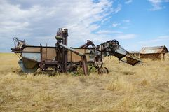 Old abandoned farming equipment. Old abandoned harvesting  comebine in a field in Wyoming Stock Image