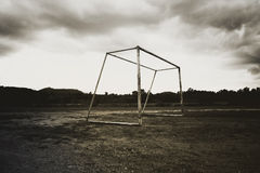 Old abandoned football goal post standing on field Stock Photos