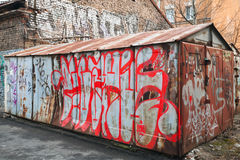 Old abandoned garage with chaotic grungy graffiti Stock Photo