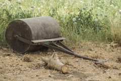 Old abandoned garden roller in meadow Stock Image