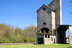 Old Abandoned Grain Elevator. An old abandoned wooden grain elevator by a railroad track Royalty Free Stock Photos