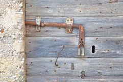 Old, abandoned, gray, wooden door with padlock Royalty Free Stock Images
