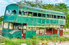 Old abandoned green double decker bus with broken and shattered window glass, damaged and left to rust Stock Photos