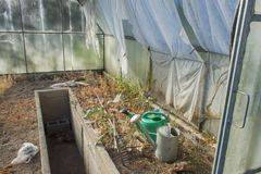 Old and abandoned greenhouse gardening. Gardening cans and rakes. Preparing for the cultivation of vegetables. Stock Photography