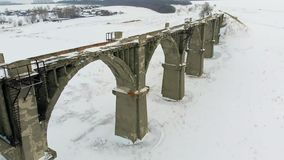 Old railway aqueduct, stone bridge. snow, winter time. aerial, copter shoot. Old abandoned historic railway bridge, snow, winter time. panorama, spans over the stock footage