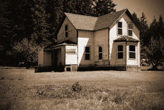 Old abandoned homestead farm house. An old decaying abandoned two story homestead farm house in a field. Sepia. Noise added for effect stock images