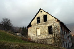 Old abandoned house. Against the dark cloudy sky Stock Photo
