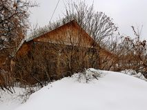 Old abandoned house with a broken window on the background of snow in winter stock photos