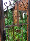Old abandoned house. Covered with grass, bushes and leaves. Old rusty metal gates and grates are not opened for a long time stock photography