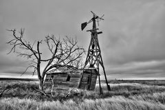 Old Abandoned House in an Empty Field. Old abandoned house and windmill in an open field in Colorado Royalty Free Stock Photo