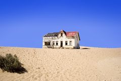 Old abandoned house at kolmanskop Namibia. Old abandoned house in desert at kolmanskop Namibia with clear blue sky Stock Photo