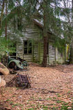 Old abandoned house near car cemetery. With green trees and red ground. A old car is sitting on the ground and also a old car seat Royalty Free Stock Photo