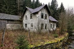 Old abandoned house with open windows by the river stock photography